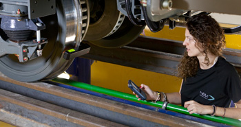 A worker inspects a train with the aid of her tablet